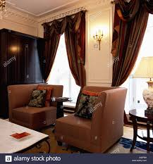 corner armchairs and heavy brown silk curtains on tall windows in