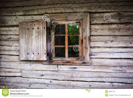 small window in the wall of an old wooden house stock photos