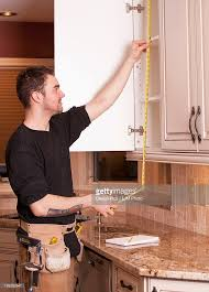 carpenter measuring and installing new kitchen cabinets stock
