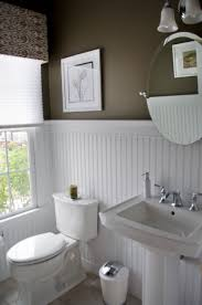 high contrast powder room dark walls white beadboard wainscot