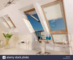 large velux window open with blind and blue sky with table and