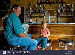 child in french man and child sitting in french bar sud touraine france stock