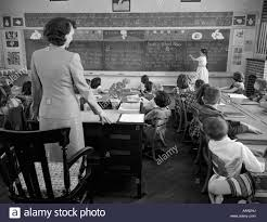 1950s at front of classroom using pointer to read through