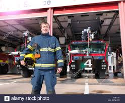 portrait of fireman in front of fire engines in airport fire
