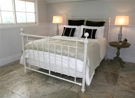 white metal bed frame with headboard and white grey bedding set on