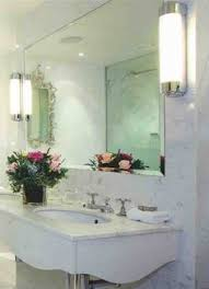 bright track lamps above oak vanity and white sink near simple