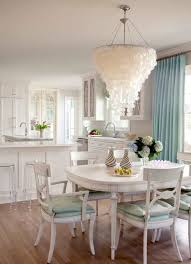 large capiz shell chandelier over white dining table and chairs in