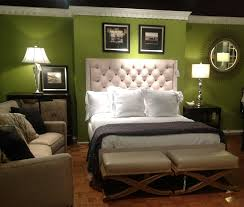 green painted bedroom wall with white leather upholstered bed