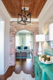 White Foyer Table by Hallway Brick Wall With Arched Door Warm Wood Ceiling With White