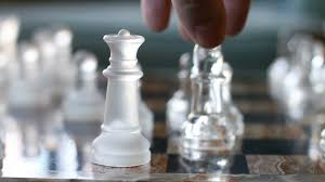 bishop takes queen glass chess piece move on board game stock