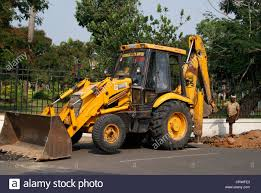 jcb earth mover digging the tarred road for underlying pipe stock