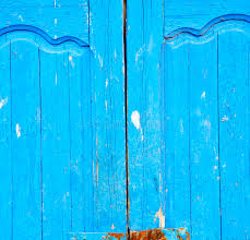 dirty stripped paint in the blue wood door and rusty nail stock