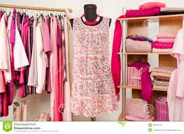 dressing closet with pink clothes arranged on hangers and shelf