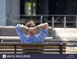 bench berlin a relaxed man sitting on a park bench berlin germany stock photo