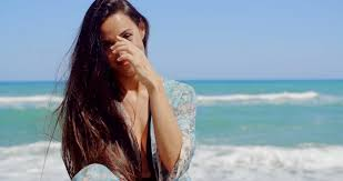 black hair for the beach close up happy young pretty woman at the beach holding back her
