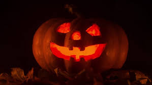 a scary halloween pumpkin lantern in the window seamless loop