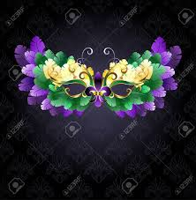 black mardi gras mardi gras mask of green purple and yellow feathers on a black
