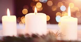 slow twinkling christmas lights burning candle in front of abstract blurred christmas lights bokeh