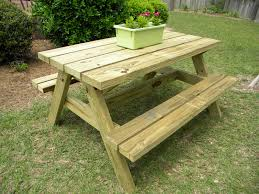 simple outdoor wooden picnic table with benches built in made from