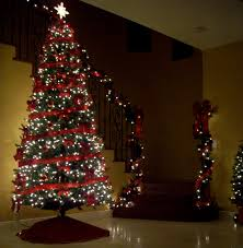 a white lighted christmas tree and lighted garland coming down the