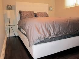 white floating bed frame complete with grey bedding set and white