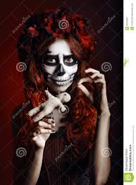 young woman with muertos makeup sugar skull piercing voodoo doll