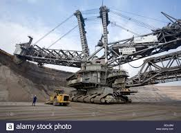 man standing by a wheel loader and a bucket wheel excavator stock