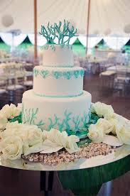 the three tier wedding cake is decorated with turquoise swags and