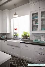 white cabinets black counter marble backsplash and an