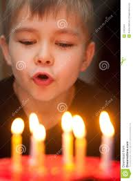 boy blowing out candles on birthday cake stock images image