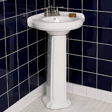 bathroom corner pedestal sink in black and white bathroom design