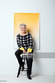 mature woman in funky dress and yellow background stock photo