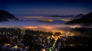houses winter resort town blanket fog city valley lights