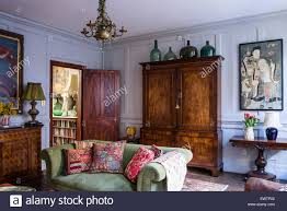 living room armoire indian and antique french cushions on green sofa in living room with
