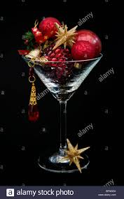 cocktail photography red and gold christmas decorations in cocktail glass against a