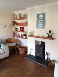 eclectic living room with oak floating shelves and log burner nice and cosy i like the simple fire place with wooden mantle piece