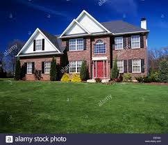two story brick house with landscaped lawn and red front door