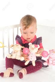 Old Baby Cribs by Cute Baby 1 Year Old Sitting On Crib Holding Soft Toys