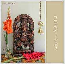 Statues For Home Decor by Wooden Ganesha Statue Flanked By Flowers And Brass Hanging Bell
