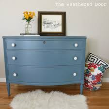 a smokey blue dresser with white knobs the weathered door