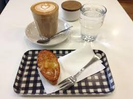 latte with orange friand a small french cake often mistaken for