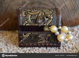 an ornamental jewelry box and a white pearl necklace a