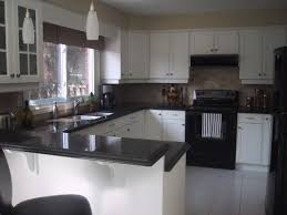 black and white appliance reno kitchen with white cabinets and black appliances counter for the