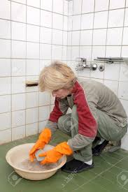 middle age woman cleaning dirty old tiles in a bathroom stock