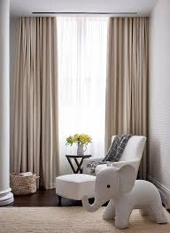 white and beige boy nursery with beige striped curtains