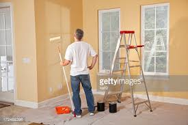 painting for home interior house painter standing on ladder painting a large wall stock photo