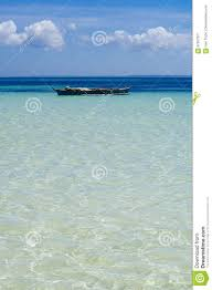 transparent tropical ocean with white sand on the bottom stock