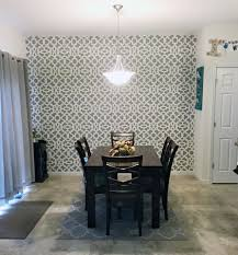 a diy stenciled dining room accent wall in an open floor plan