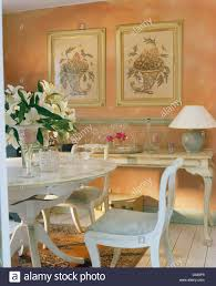 white painted table and chairs in cottage dining room with floral