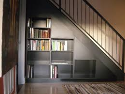 black staircase grey bookcase under black staircase on ceramics flooring and white